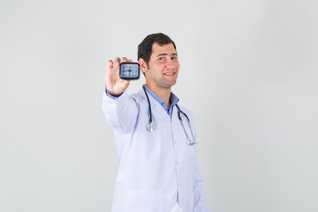Mannelijke arts in de witte klok van de vachtholding en op zoek vrolijk