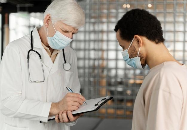 Mannelijke arts in gesprek met de patiënt