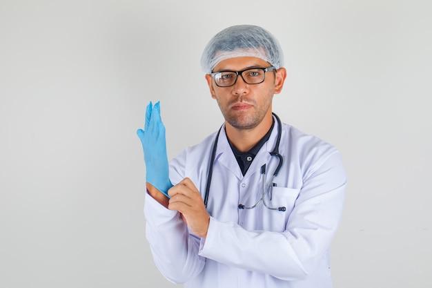 Mannelijke arts in medische witte op handschoen zetten en robe die nadenkend kijken