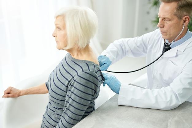 Mannelijke arts in steriele handschoenen die een stethoscoop op de rug van een vrouwelijke patiënt zet en haar adem controleert