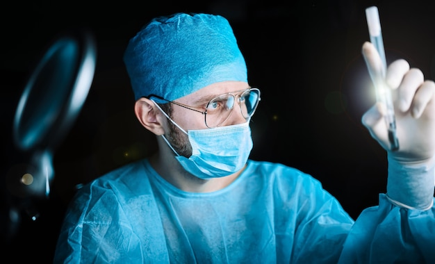 Mannelijke arts in uniform werkt met medische reageerbuizen in een ziekenhuis
