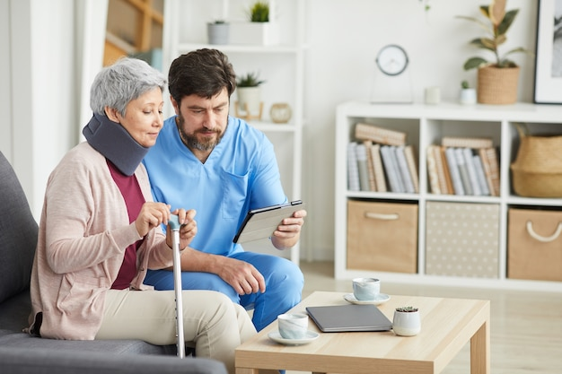 Mannelijke arts in uniform zittend op de bank samen met senior vrouw die hij met behulp van digitale tablet en vertelt over haar diagnose