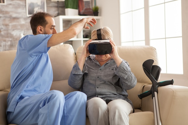 Mannelijke arts in verpleeghuis die hogere vrouw helpt om vr-hoofdtelefoon te gebruiken.