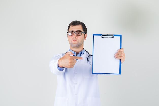 Mannelijke arts in witte jas, bril wijzende vinger naar klembord en op zoek naar serieus
