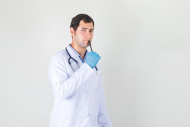 Mannelijke arts in witte jas, handschoenen die pen op lippen houden en nadenkend kijken