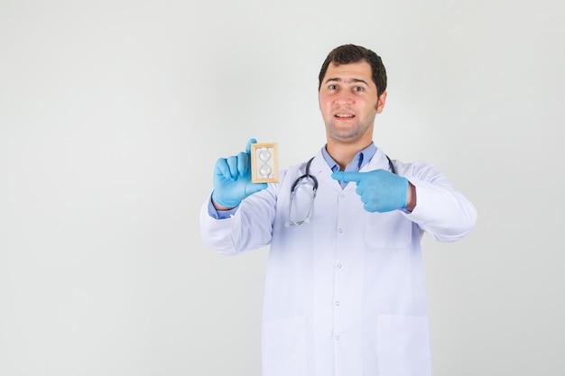 Mannelijke arts in witte jas, handschoenen wijzende vinger naar zandloper en op zoek vrolijk