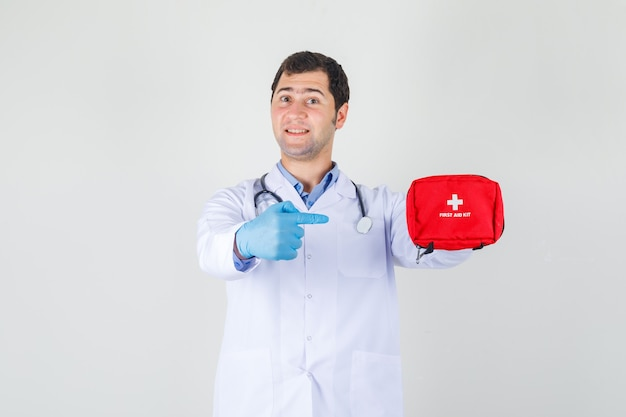 Mannelijke arts in witte jas, handschoenen wijzende vinger op ehbo-kit en op zoek vrolijk