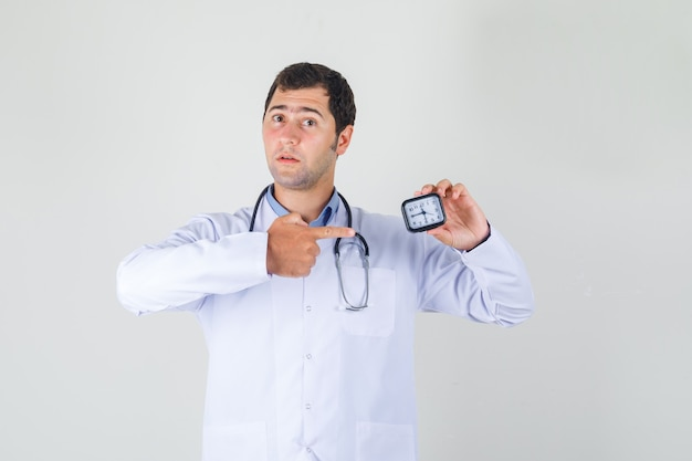 Mannelijke arts in witte jas wijzende vinger op klok en op zoek voorzichtig