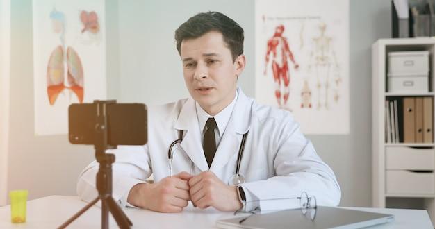 Mannelijke arts met behulp van mobiele telefoon voor videoconferenties