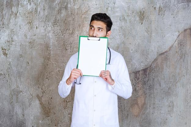 Mannelijke arts met een stethoscoop die de geschiedenis van de patiënt vasthoudt en er attent uitziet.