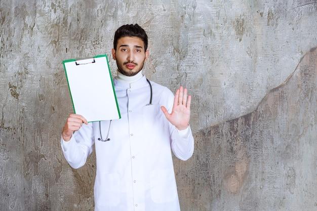 Mannelijke arts met een stethoscoop die de geschiedenis van de patiënt vasthoudt en iets tegenhoudt.