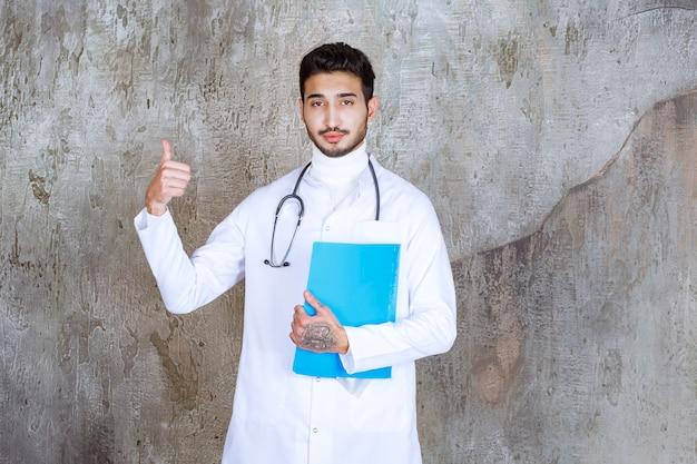 Mannelijke arts met een stethoscoop die een blauwe omslag houdt en positief handteken toont.
