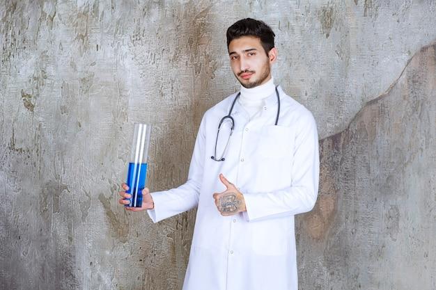 Mannelijke arts met een stethoscoop die een chemische kolf met blauwe vloeistof binnen houdt en succesvol handteken toont.