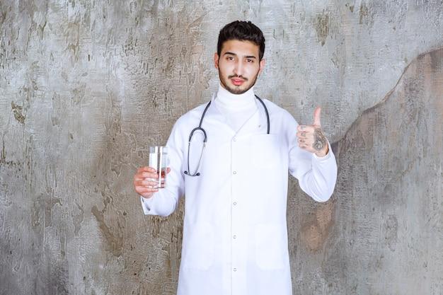 Mannelijke arts met een stethoscoop die een glas zuiver water houdt en positief handteken toont.