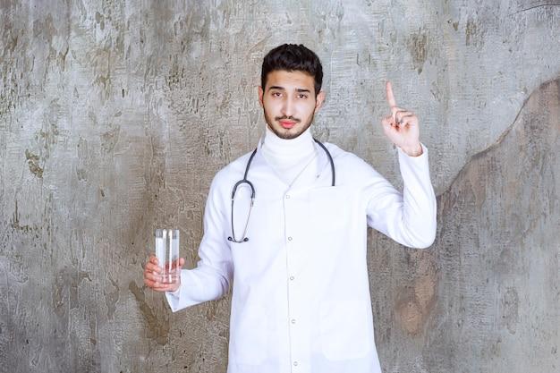 Mannelijke arts met een stethoscoop die een glas zuiver water vasthoudt en ergens aan denkt.