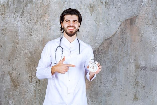 Mannelijke arts met een stethoscoop die een wekker houdt