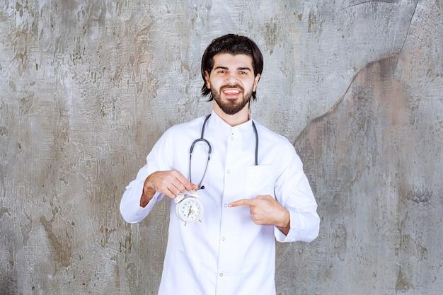 Mannelijke arts met een stethoscoop die een wekker houdt.