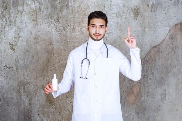 Mannelijke arts met een stethoscoop die een witte fles met handdesinfecterend middel vasthoudt en een goed idee denkt of heeft