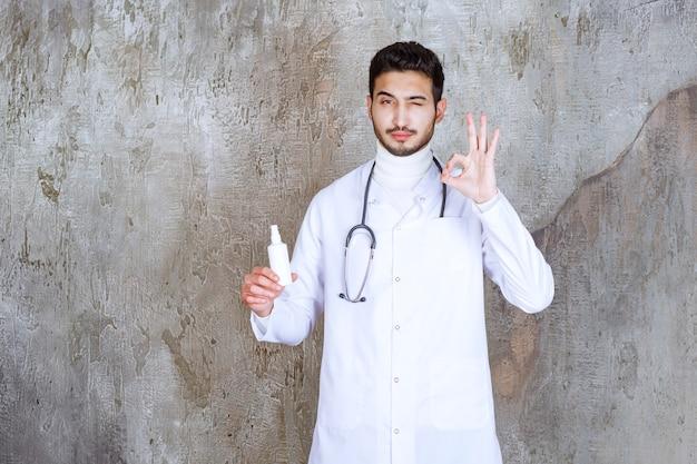Mannelijke arts met een stethoscoop die een witte fles met handdesinfecterend middel vasthoudt en een positief handteken toont