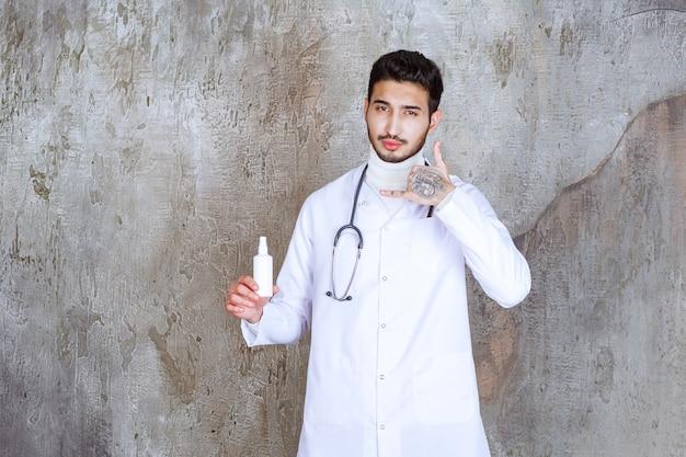 Mannelijke arts met een stethoscoop die een witte fles met handdesinfecterend middel vasthoudt en om een telefoontje vraagt