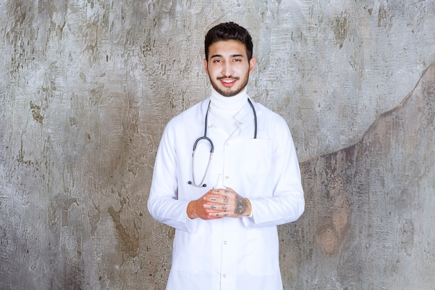 Mannelijke arts met een stethoscoop die een witte fles van het handdesinfecterend middel houdt.