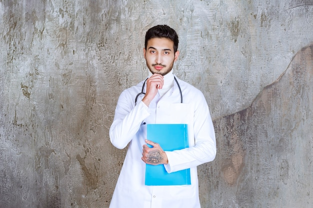 Mannelijke arts met een stethoscoop met een blauwe map, denken en plannen.
