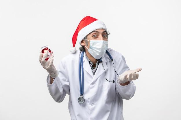 Mannelijke arts met nieuwjaar boom speelgoed vloer gezondheid covid virus