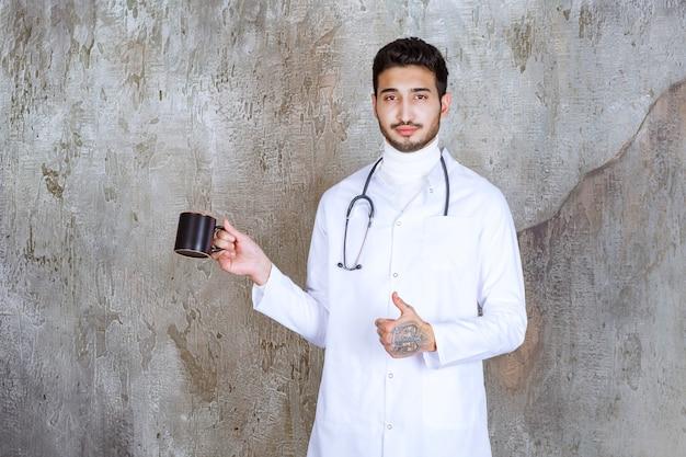 Mannelijke arts met stethoscoop die een kopje koffie vasthoudt en geniet van de smaak