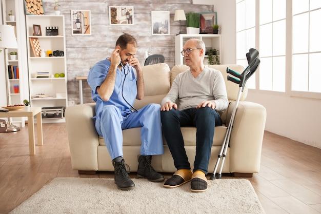 Mannelijke arts met stethoscoop in verpleeghuis om het hart van de oude man te controleren.