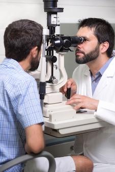 Mannelijke arts oogarts is het controleren van de visie van het oog van de knappe jonge man in de moderne kliniek