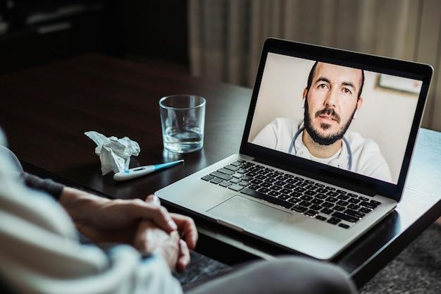 Mannelijke arts op laptopscherm tijdens videogesprek met patiënt met coronavirus-symptomen
