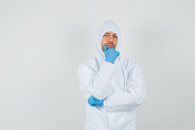 Mannelijke arts permanent denken pose in beschermend pak