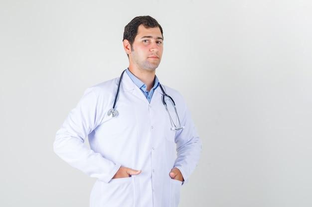 Mannelijke arts permanent met handen in zakken in witte jas en op zoek naar vertrouwen. vooraanzicht.