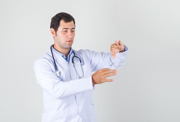 Mannelijke arts spuit voor injectie in witte jas te houden