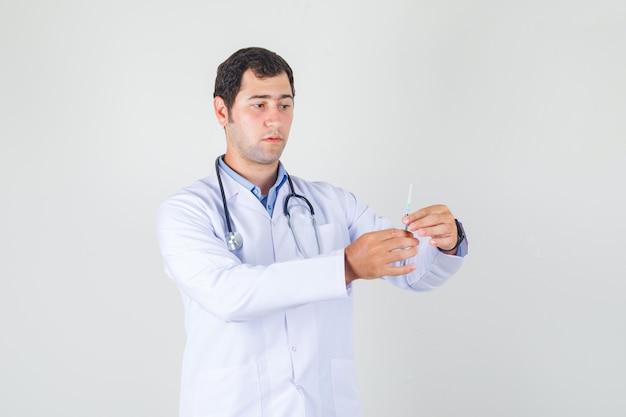Mannelijke arts spuit voor injectie in witte jas vooraanzicht te houden.