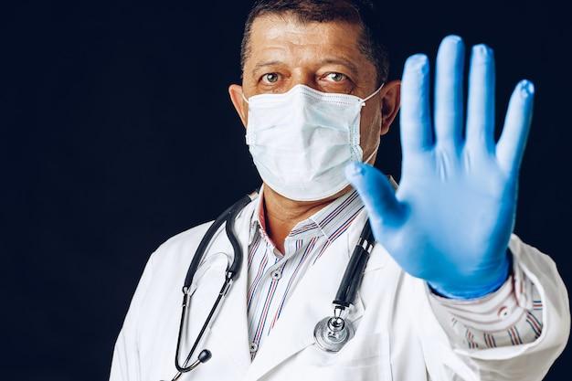 Mannelijke arts stopbord tonen, medische masker en handschoenen dragen.
