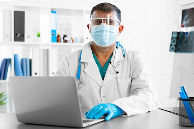 Mannelijke arts van middelbare leeftijd in gelaatsscherm en masker aan de tafel op zijn kantoor zitten en werken