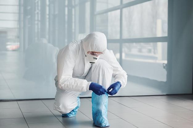 Mannelijke arts wetenschapper in laboratoriumjas, defensieve brillen en masker dragen van beschermend materiaal op de benen