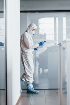 Mannelijke arts wetenschapper in laboratoriumjas, defensieve brillen en masker kladblok in handen houden