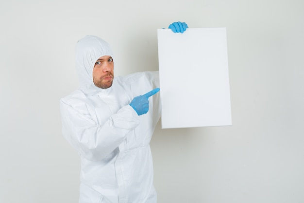 Mannelijke arts wijzend op leeg canvas in beschermend pak