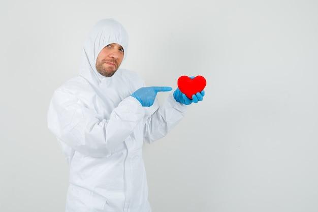 Mannelijke arts wijzend op rood hart in beschermend pak