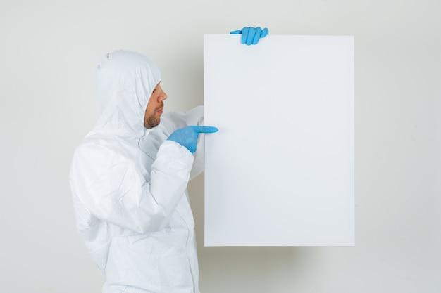 Mannelijke arts wijzend op wit bord in beschermend pak