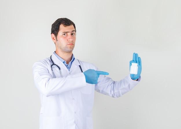 Mannelijke arts wijzende vinger op fles pillen in witte jas, handschoenen en op zoek strikt