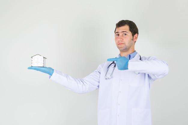 Mannelijke arts wijzende vinger op huismodel in witte jas, handschoenen vooraanzicht.