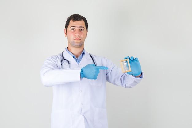 Mannelijke arts wijzende vinger op zandloper in witte jas, handschoenen en op zoek naar ernstig. vooraanzicht.