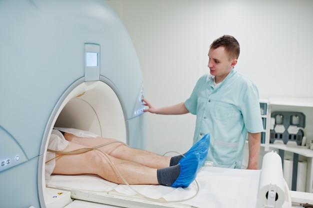 Mannelijke arts zet magnetische resonantie beeldvormingsmachine aan met patiënt binnen.