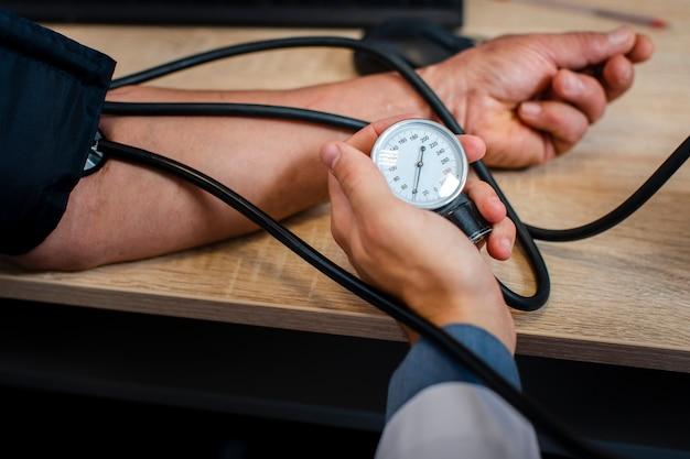 Mannelijke artsenhand die spanning meten
