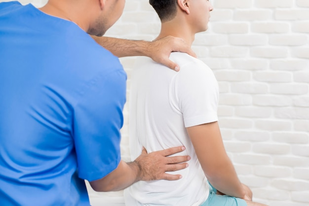 Mannelijke artsentherapeut die lage rugpijnpatiënt in kliniek of het ziekenhuis behandelen