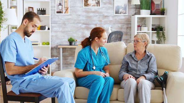Mannelijke assistent die aantekeningen maakt op het klembord terwijl de vrouwelijke arts praat met een oudere vrouw in het verpleeghuis