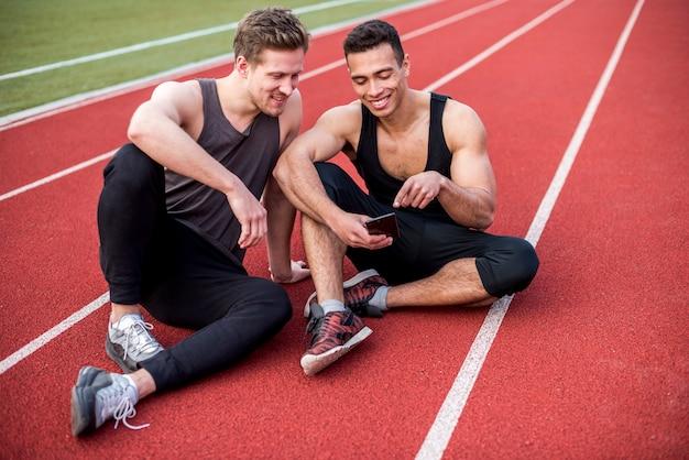 Mannelijke atleet die iets op mobiele telefoon tonen aan zijn vrienden die op rasspoor zitten